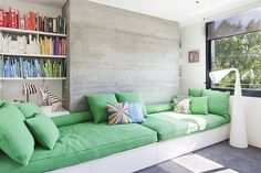 plush green seating, color grouped books.
