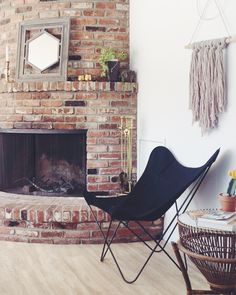 vintage butterfly chair in a mid century modern california air bnb home boho chic brick fireplace and yarn wall hanging