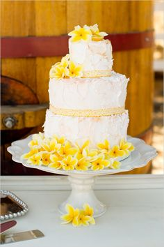 white wedding cake with plumeria... Maybe frosted a little better so grandma doesn't have a heart attack...
