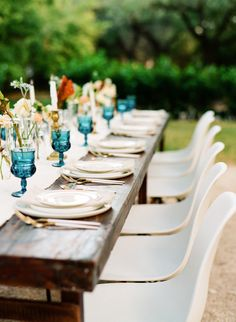 White Eames Chairs and a Farm Table with white, pink and gold silverware and blue goblets White Eames Chair, Eames Chairs, Dark Color Palette, Dark Colors, Wedding Ceremony Seating, Wedding Table, Wedding Shoot, Blue Wedding, Traditional Furniture