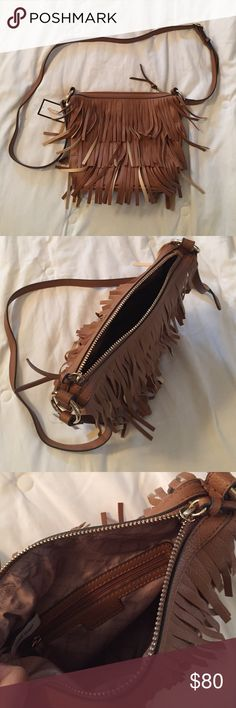 """NWT Nine West tan fringed crossbody bag trendy! Be totally on trend with this fringed fun cross body bag by Nine West. Brand new. If it doesn't sell I'll keep it but I already have one similar! Inside zip pocket. Made made materials. Looks like leather. Adjustable strap is about 45"""" long. Bag is 8.5""""x 9.5"""". Perfect for Fall with a plaid top, jeans and boots. Seen all over the pages of magazines for the top trend for the season. Add a PSL from Starbucks and you're set! ❤️ Nine West Bags…"""