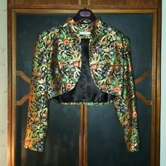 Vintage bolero jacket Beautiful vintage floral patterned metallic short bolero jacket. Lots of gold lurex thread throughout with embroidered metallic jewel-toned flowers all over. It has internal shoulder pads to give the garment a more structured silhouette which can easily be removed. Labeled vintage size 8 but will fit S/M best. Such a stunning and sparkly little piece! Would look great with black skinnies and stilettos! In excellent vintage condition! Hit me up with any questions or for…