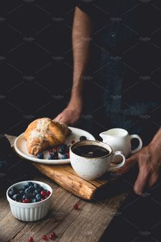9f162d3b4194 Hands holding wooden tray with continental breakfast croissant, coffee,  cream and fruits by The