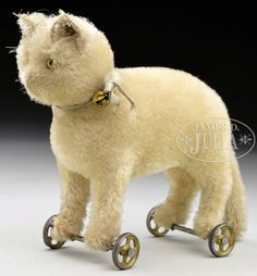 EARLY WHITE STEIFF MOHAIR CAT WITH BUTTON ON WHEELS, CIRCA 1909.