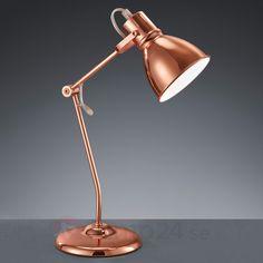 Denna lilla bordslampa av metall med formskön design passar i många olika rum: på skrivbordet i hemmakontoret, i sovrummet på nattduksbordet, i en hylla eller på en byrå.