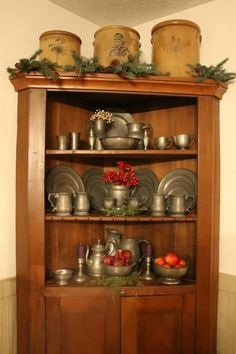 Pottery and pewter displayed on a corner cupboard