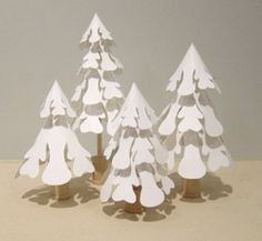 Our favorite part of these Paper Snowflake Pines is the shadow they cast on the table. They look like little snowflakes. Plus, because these DIY paper crafts are white, they'll go with any home decor.