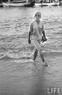 Photo of actress Sue Lyon walking on beach on location during the filming of The Night of the Iguana by Gjon Mili, 1963. Cast    Richard Burton: Reverend Dr. T. Lawrence Shannon  Ava Gardner: Maxine Faulk, widowed owner of the beach hotel  Deborah Kerr: Hannah Jelkes, wandering artist  Sue Lyon: Charlotte Goodall, underage girl who tries to seduce Shannon  James Ward: Hank Prosner, bus driver  //  Sue Lyon also played Lolita in the same titled movie.