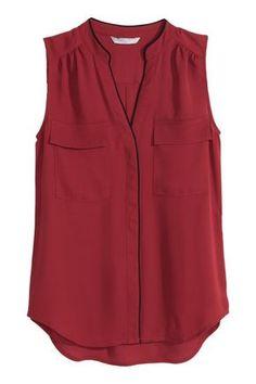 Blusa de tela sin mangas con detalles en color de contraste. Escote de pico y cierre oculto de botón en la parte delantera, bolsillos superiores con solapa.