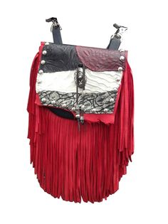 "RENEGADE MARTY - made of velvety soft black deerskin with a 7"" red deerskin fringe. The flap features white laser cut hair-on-hide and red, black and silver printed leather. The centerpiece is a silver design with suede laces and silver beads. Etched silver metal studs trim the outline of the bag. Wear bag clipped to belt loops for hands-free carrying of your essentials. Interior includes a leather strap. Add the strap when you want a completely different look."