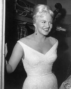 Peggy Lee, white portrait collar dress, dangly earrings.