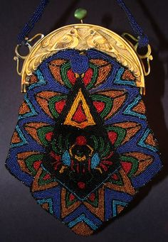 The beaded bag has a distinct Egyptian Revival theme. So do the hooks where the celluloid chain attaches to the frame. But the birds are a stylized version of the Kiwi.