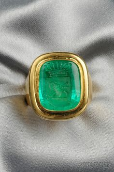 18kt Gold & Emerald Intaglio Ring, bezel-set with an emerald intaglio measuring approx. 18.00 x 25.00 mm, weighing approx. 11.05 cts., carved with an armorial depicting a ram, surmounted by a coronet