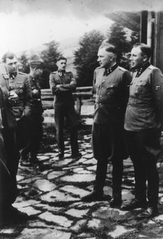 Nazi officers stand on a terrace of Solahuette, the SS retreat outside of Auschwitz. Pictured on the far left is Dr. Josef Mengele. Pictured on the right are Commandant Richard Baer and his adjutant Karl Hoecker. The picture was taken during a party celebrating Rudolf Hoess' completion of tenure as commandant of Auschwitz, and the handover of power to Baer.