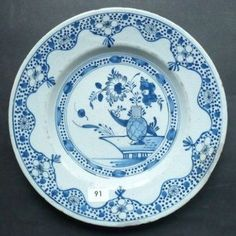 DELFT. Assiette ronde décorée en camaïeu bleu d'un vase fleuri encadré de lambrequins fleuris. Fin du XVIIIème siècle