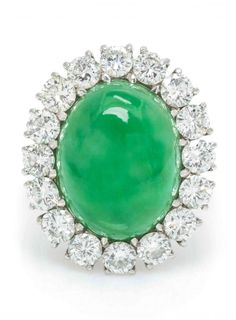 A Platinum, Jadeite Jade and Diamond Ring, containing one oval double cabochon cut jadeite jade measuring approximately 16.11 x 12.56 x 9.14 mm, surrounded by 16 round brilliant cut diamonds weighing approximately 2.40 carats total, later hinged shank.
