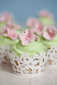 Cupcakes with light green frosting, pink sugar flowers, and fancy paper holders