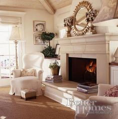 Quaint setting with big mirror and pretty chairs on either side of the fireplace.