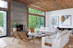 concrete fireplace/chimney juxtaposed with rough-wood ceiling and window framing. At fashion designer Jenni Kayne's family-friendly California home, a fireplace surround made of board-formed concrete anchors the living room.