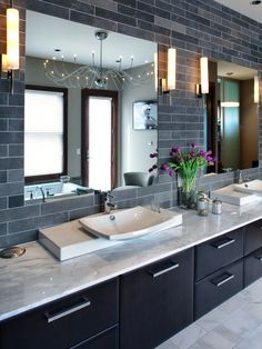 The gray tiled double vanity in this contemporary bathroom features two mirrors, two sinks, four wall sconces and an interesting contemporary pendant light reflected in one of the mirrors.