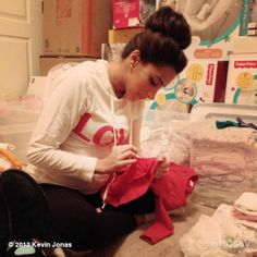 Danielle Jonas going through all the baby cloths so much pink!