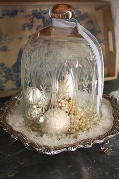 Beautiful vignette on a silver tray....ornaments, pearls and cut glass cloche...with a touch of faux snow!