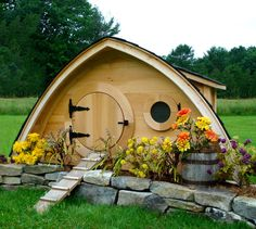 That's a chicken coop that looks like a Hobbit hole.  Yep... Maybe instead of a chicken coop it could be a play house?...