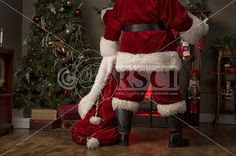 A real authentic Christmas photo of Santa Claus in front of a fireplace at home delivering present to the kids Real Santa Pictures and This images can be licensed to use at realsantaimages.com | Do Not Use Without A License