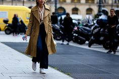 Paris Haute Couture Street Style: A woman wearing jeans and a trench coat after a fashion show in Paris, France