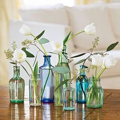 Vintage sea glass bottles used as bud vases would add texture and heigh to dining table centerpieces