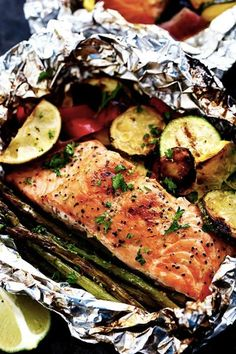 Grilled lime butter salmon in foil with summer veggies. 15 Foil-Packet Dinner Recipes that Make Cleanup a Breeze #purewow #dinner #grilling #easy #food #recipe #cooking #foilpacketrecipes #foilpackets #campingrecipes #summerveggies