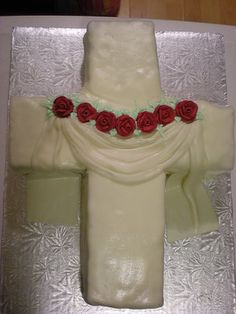 The quality of this decorating is not great, but I like the idea.  Cross cake decorated for my friends baptism. Used Marshmallow fondant as it allows better draping (softer).  The leafs are just icing and the roses are pre-made ones purchased from the store - again, I don't have ANY tools to work with, except the one tip I purchased specifically for this project.