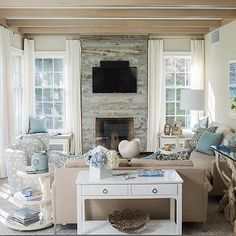 Liz Levin Interiors - living rooms - cottage living room, cottage living room ideas, box beams, living room box beams, reclaimed wood fireplace, distressed wood fireplace, fireplace lined with tv, tv over fireplace, over the fireplace tv, freestanding bench, storage bench, living room bench, white curtains, light brown sofas, L shaped sofas, branch accent tables, sofa table, white sofa table, round tiered table, swivel chair, living room french doors, french doors in living room,