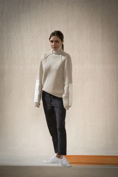 Victoria Beckham in an ivory cable-knit turtleneck sweater + grey slouchy trousers + white sneakers at her Fall 2016 show