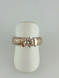 Mokume Gane engagement ring with rose gold curved V channel holding a 1.00ct. diamond. The perfect combination of a unique diamond and a colorful mix of golds.