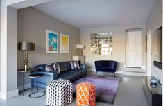 Gorgeous family living area for watching TV. Pops of colour against the Elephants Breath Farrow & Ball wall colour. Blue italian leather sofa, hexagonal colourful stools. Mirrored sidetables , blue velvet love seat with purple and grey designers guild rug. Feature mirror brings in light in this Edwardian home extension and renovation Purple Leather Sofas, Home Living Room, Living Area, Elephants Breath, Italian Leather Sofa, Color Pop, Colour, Edwardian House, House Extensions