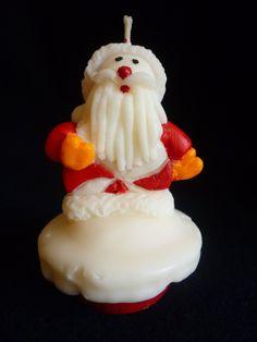 Vela em formato de cup cake com Papai Noel, produzida em cera a base de óleo vegetal, acondicionada em caixa de acetato transparente. <br> <br>Pode ser aromatizada nas essencias de chocolate, baunilha, cravo, canela, mel, noz moscada. <br> <br>Vela pintada a mão com tinta a base de água