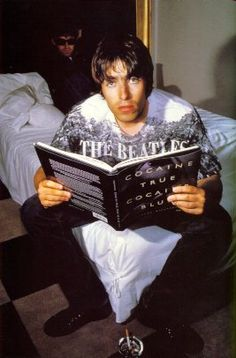 Liam wearing a Beatles top and reading a book about coacaine, oh and noel in the background.