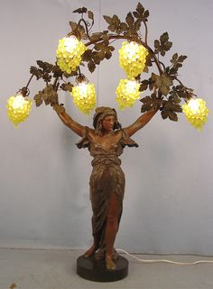 A circa-1920 metal Art Nouveau landing light of a lady with grapes, with marble base.