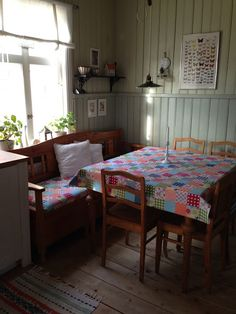 patchwork table cloth, tiny shelves, hanging light, plants and wood chairs