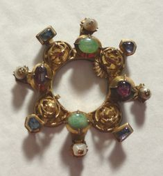 Annular brooch, 14th century, made in Hungary (probably): gold, emeralds, pink and blue sapphires, pearls; of circular form with eight bosses; the bosses alternately openwork set with a winged beast, emerald, pink sapphire; from each boss a projection set alternately with pearls and sapphires;
