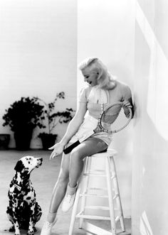 Ginger Rogers, apparently about to play tennis with a dalmatian.