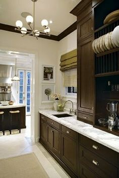 Contemporary and traditional elements (Bin pulls, cabinet to countertop, marble, modern chandelier