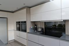Gloss cashmere and jasmine cream kitchen units, handleless design in modern kitchen with oak laminate splashback and grey quartz / silestone wortops and american style refridgerator. Cashmere Gloss Kitchen, Grey Gloss Kitchen, Kitchen Diner Lounge, Kitchen Diner Extension, Cream Kitchen Units, Kitchen And Bath, Grey Kitchens, Splashback, House Extensions