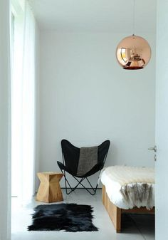 bare white space with a butterfly chair, plenty of cowhide, sheepskin, and fur, and a single copper pendant