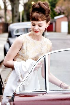 Top curls, dangled earrings and a rosey gold dress.