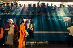A ewlywed bride in her bright orange kurta, frozen in a shaft of light on a train platform in Dhaka, Bangladesh, India - Photo: Shahnewaz Ka...