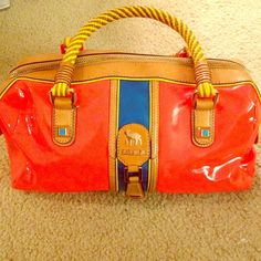 Very rare L. A. M. B. bright orange purse Very rare lamb by Gwen Stefani bright orange bag with colored and brown leather accents. Bright colors are the in thing right now, this bag couldn't be more perfect. It's a bowling style bag. Very lightly used and minimal signs of wear. Amazing color and quality! L.A.M.B. Bags