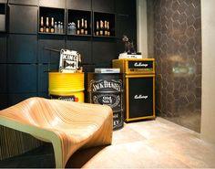 """Bar e Sala de Jogos. """"O arquiteto Júlio Mesquita apostou em uma linguagem industrial no espaço que apresenta revestimentos com aparência de aço e concreto. A poltrona com formas arredondadas quebra a rigidez e reforça a informalidade, também citada em complementos como tonéis customizados e um amplificador de guitarra."""" No site Casa"""