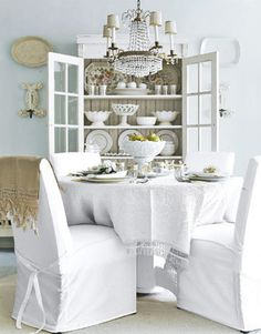 Very feminine dining area.  Slipcovers, cupboard with open doors.  All the colors carefully planned